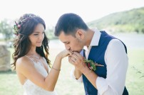 happy groom in a dark blue suit kisses the hand of his beautiful bride in a white wedding dress outdoors. focus on bride